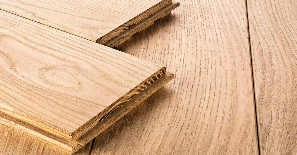 enkele planken massief parket liggen op een houten vloer